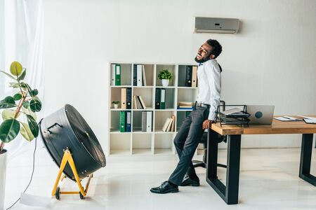 Exhausted African american businessman standing in front of electric ventilator in office