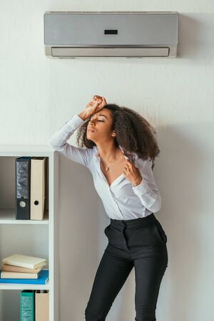 Exhausted African american businesswoman holding hand on head while standing under air conditioner in office Stockfoto