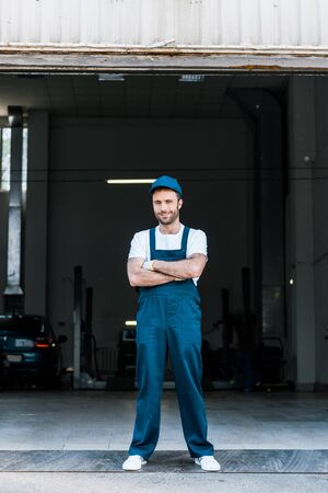Handsome bearded car mechanic standing with crossed arms