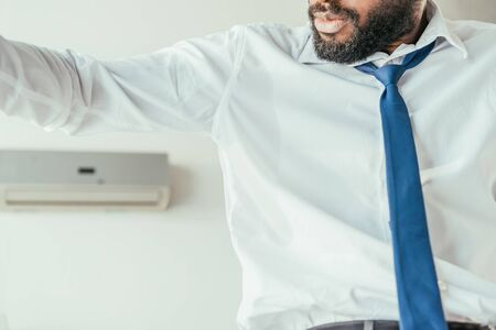 Cropped view of African american businessman looking at sweaty shirt while suffering from heat Reklamní fotografie