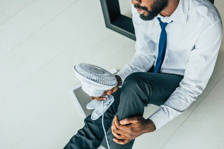 Cropped view of African american businessman sitting on floor and holding blowing electric fan