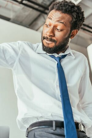 Irritated African american businessman looking at sweaty shirt while suffering from summer heat in office Reklamní fotografie