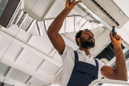 Vue à faible angle d'un bricoleur afro-américain réparant un climatiseur avec un tournevis Banque d'images