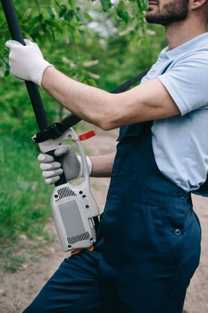Partial view of gardener in overalls trimming trees with telescopic pole saw in garden