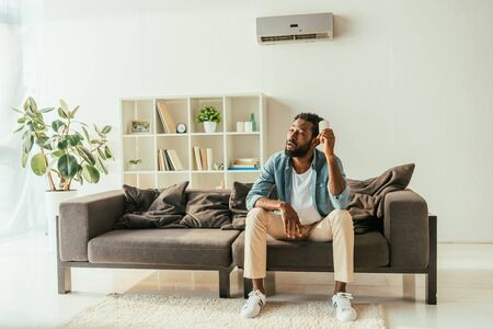 Tired African american man sitting on sofa and holding air conditioner remote controller while suffering from heat at home