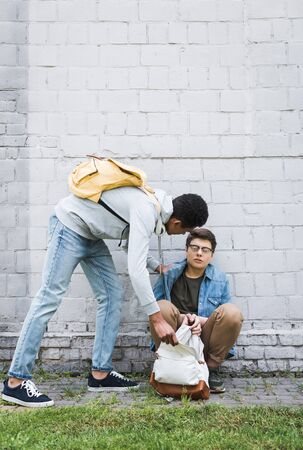 Aggressive African american boy taking backpack from frightened boy in glasses Zdjęcie Seryjne