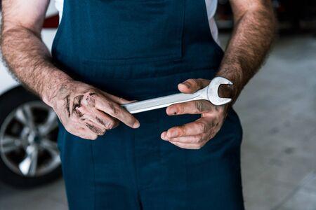 Vista recortada del mecánico de automóviles con barro en las manos sosteniendo una llave de mano en la estación de reparación de automóviles Foto de archivo