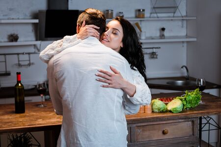 Woman with closed eyes embracing man at kitchen in evening