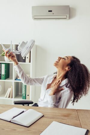 Pretty African american businesswoman sitting at workplace and holding electric fan while sitting at workplace in office