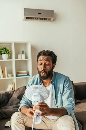 Handsome African american man holding blowing electric fan while sitting on sofa and suffering from heat at home Reklamní fotografie