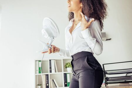 Partial view of African american businesswoman holding desk fan while suffering from heat in office Stock Photo