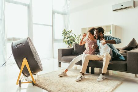 Excited African american man and woman sitting on sofa in front of blowing electric fan Stock Photo