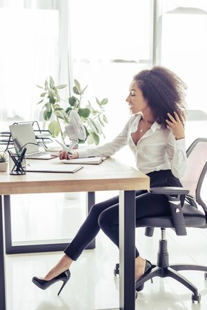 Attractive African american businesswoman sitting at workplace and holding electric fan while suffering from heat in office Stock Photo