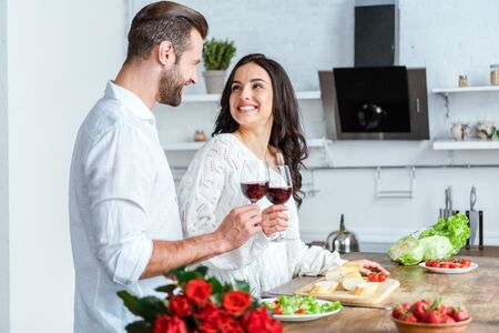 Happy man clinking glasses of red wine with smiling woman at kitchen Foto de archivo