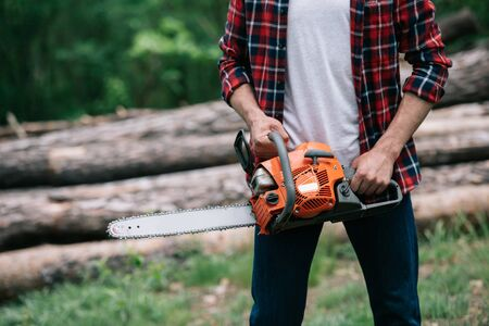 Cropped view of lumberjack holding chainsaw while standing near logs in forest