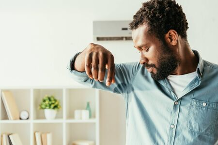 Displeased African american man looking at sweaty shirt while suffering from heat at home