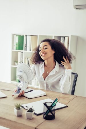 Cheerful African american businesswoman holding electric fun while suffering from heat in office Stock Photo