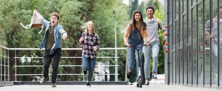 Panoramic shot of happy friends smiling, running and riding scooter