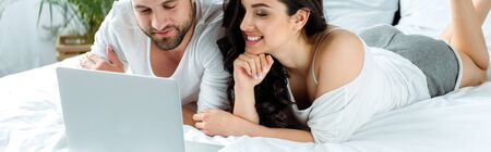 Happy couple using laptop together while lying in bed, illustrative editorial Фото со стока