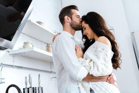 Uomo con gli occhi chiusi che abbraccia e bacia dolcemente la donna