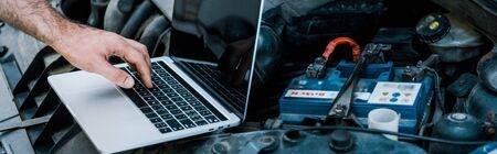 Photo panoramique d'un mécanicien automobile utilisant un ordinateur portable avec un écran vide près de la voiture Banque d'images