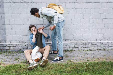 Wütender und brünetter afroamerikanischer Junge, der verängstigten Jungen in Gläsern schikaniert Standard-Bild