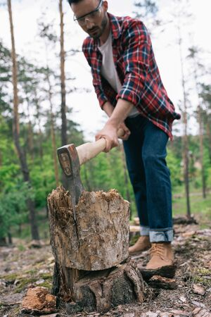 Selective focus of lumberman in plaid shirt and denim jeans cutting wood with ax in forest