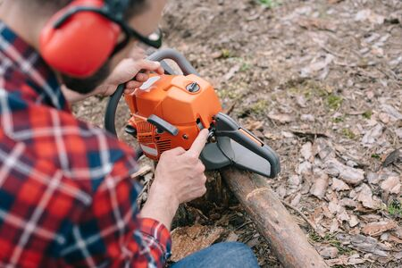 Selective focus of lumberjack in hearing protectors repairing chainsaw in forest Stockfoto