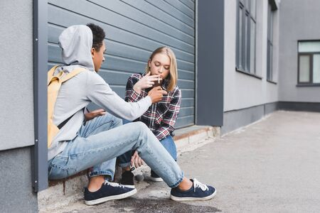 African american boy lighting cigarette of blonde and pretty teen Фото со стока