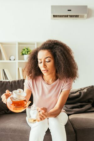 Exhausted African american woman pouring tea into cup while suffering from summer heat at home