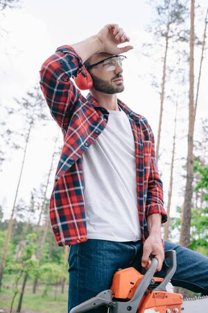 Tired lumberjack in protective glasses and earmuffs holding chainsaw and looking away in forest Stock Photo