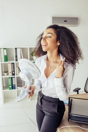 Pretty African American businesswoman standing near workplace and holding electric fan Stock Photo