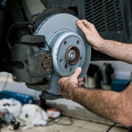 Cropped view of auto mechanic holding metallic car brake near auto