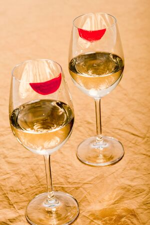 red lipstick prints on champagne glasses with alcohol on orange