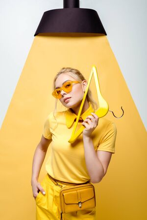 attractive blonde woman with hand in pocket holding hanger and posing on white and yellow