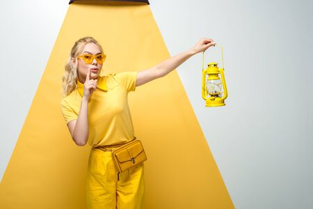 attractive blonde woman in sunglasses gesturing and holding vintage lamp on white and yellow