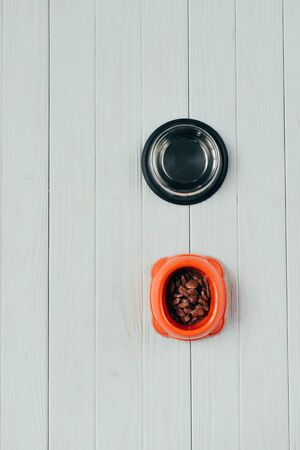 top view of bowl with pet food and empty bowl on wooden surface