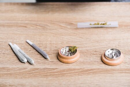 joints with medical marijuana and herb grinder on table Stok Fotoğraf