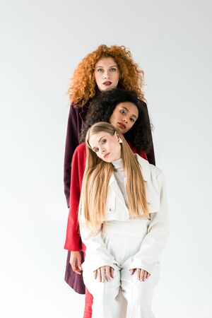blonde and redhead women standing with african american girl on white
