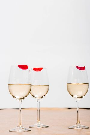 red lipstick prints on champagne glasses with alcohol on white