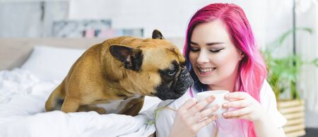 panoramic shot of happy girl with colorful hair holding cup with coffee and cute bulldog sniffing coffee