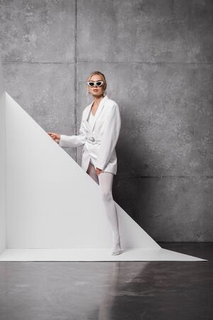 stylish woman in sunglasses posing on white and grey