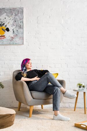 hipster girl in casual clothes relaxing on armchair at home