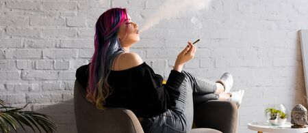 panoramic shot of hipster girl with colorful hair sitting in armchair and blowing smoke Stock Photo