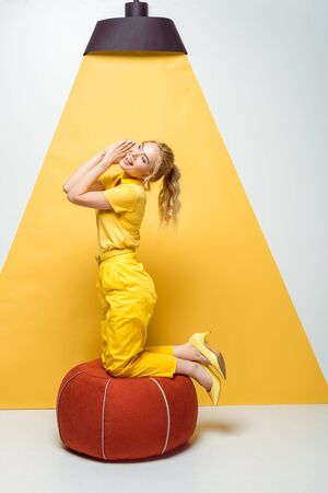 cheerful blonde girl smiling near red padded stool on white and yellow Foto de archivo