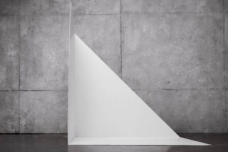 triangle shape carton near grey wall with copy space Stock Photo