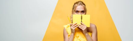 panoramic shot of blonde young woman covering face with notebook on white and yellow Stock fotó