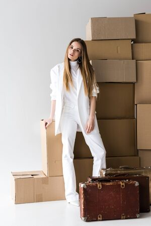 attractive blonde young woman posing near suitcases and carton boxes on white Stock Photo
