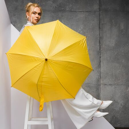 beautiful girl sitting on chair and holding yellow umbrella on white and grey