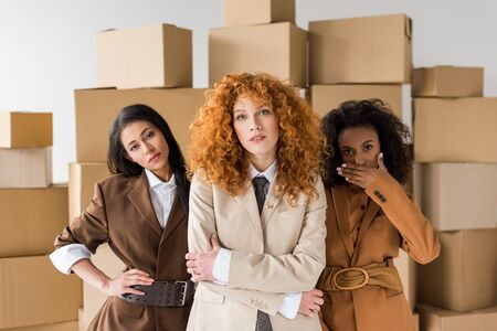 attractive redhead girl looking at camera with stylish african american young women near boxes on white